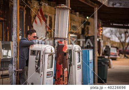 Young man smokes a cigarette at a vintage gas pump